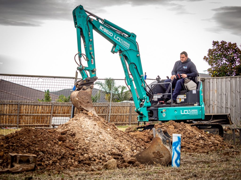 plumber on an excavator making room for pipes