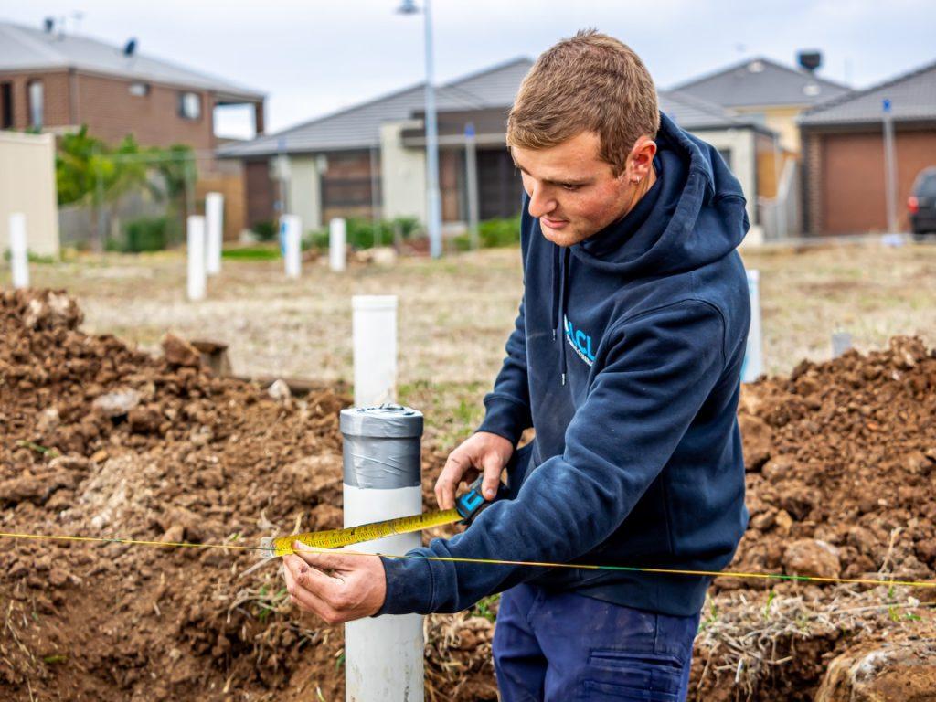 plumber measuring a pipe